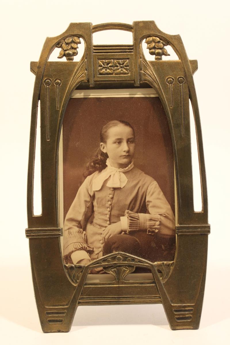Fotoram i mässingsplåt.  Fotografiet i ramen föreställer en ung flicka.