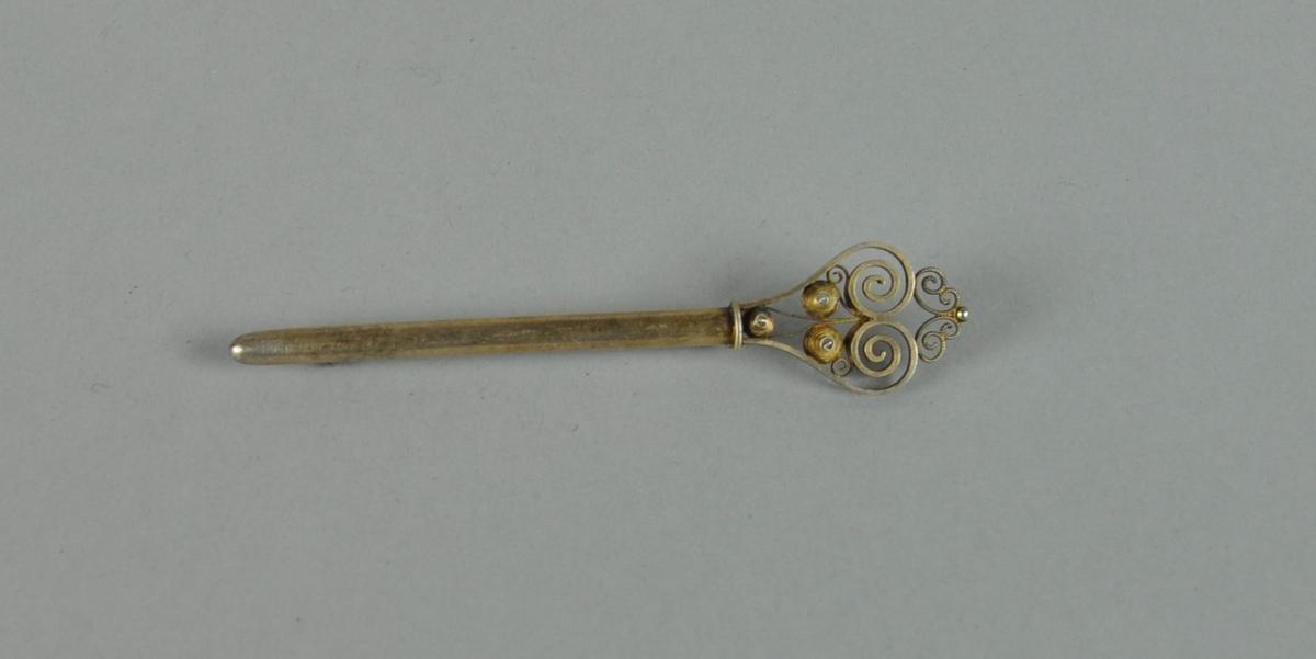 Stavformet brosje av sølv, med filigran nøkkelhodedekor.