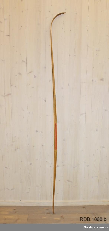 Tilnærmet jevnbred ski med liten bue. Bøy uten tupp. Avrundet bakende med litt oppbøy. Dekorert med ei brun stripe på trehvit bunn.  Stempel og klistremerker på skiet.