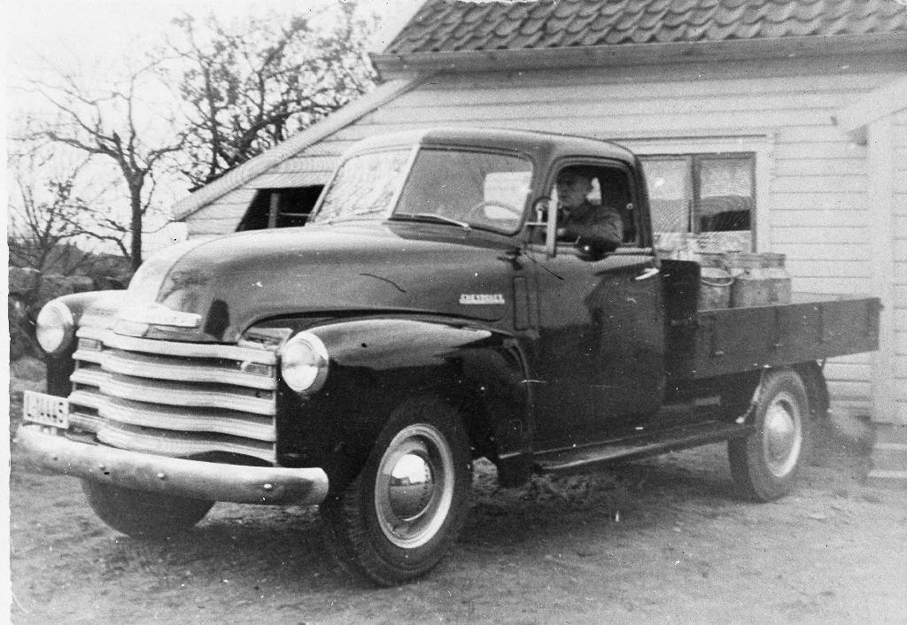 """""""Dollarglis"""" i gardsrommet til Per J. Time. Chevrlet mod ca 1950. Den vart brukt til mjølkekjøring. Sjåfør og eigar er Einar I. Time. Han fekk bilen sendt frå Canada av bror sin, Olav Time (1909 - )"""