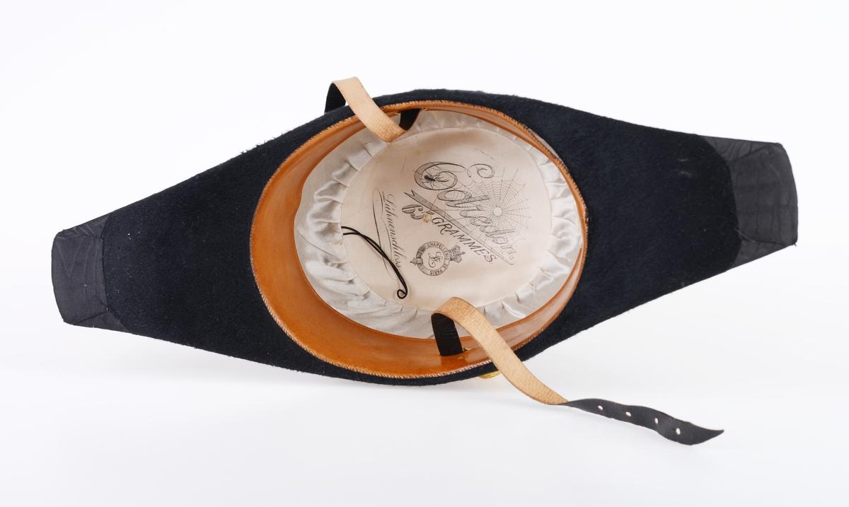 """En hatteboks (FTT.56303.01) som inneholder en snutehatt (FTT.56303.02), et bandolær (FTT.56303.03) og en epålett (FTT.56303.04).   FTT.56303.01: Hatteboksen er laget av blikk og er svartlakkert utenpå. Lokket er hengslet på baksiden. Oppå lokket er det et enkelt håndtak. I fronetn er det en hempe for hengelås. Den har to lave bein som er laget av sammenrullet blikk. Boksen har form tilpasset hatten. Esken har ikke fôr, men det ligger et papir i bunnen. FTT.56303.02: En svart uniformshatt, nærmere bestemt en snutehatt eller en tosnutet hatt. Det er gullbånddekor på hver snute. På den ene siden er det festet en stor kokarde i rødt, hvitt og blått. Over denne er det to flate gullbånd som ender i en spiss. I enden er det en gullfarget metallknapp med et anker med en kongekrone over. Hatten er laget av svart silkefloss med svarte silkebånd langs kanten. Hatten har hvitt silkefôr og svettebånd av brunt lær. På svettebåndet er det festet brune skinnreimer til å feste under haken. På den ene siden er det festet en hvit silkesløyfe. Silkefôret har informasjon om produsent, se """"Påført tekst/merker"""". Det er også bilde av en edderkoppe og et edderkoppnett. Hatten har avstivning ved hjelp av papp. Hatten er håndsydd. FTT.56303.03: Et bandolær laget av svart skinn, svart silkestoff og messing. Midjebeltet har en spenne midt foran. Spennen har motiv av et anker med en krone over. På innsiden av beltet er det sydd fast en skinnreim med metallhull til å regulere livvidden. Skulderreimen er festet i midjebeltet med metallringer. Delene til skulderreimen festes sammen med to fjærbelastende kroker. Ved sammenføyningen skulderreim og midjebelte er det påmontert en liten kjetting med krok. FTT.56303.04: En skulderklaff til uniform. Oversiden består av svarte- og gullfargede flettede snorer. På undersiden er det sydd på svart ullstoff som er like bred som klaffen. I den ene enden er det sydd på en svart knapp som ullstoffet kan festes i."""
