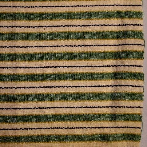 Varp ,naturvitt bomullsgarn. Inslag i ull,färgat i gult och blått, vävt i rosengång och tuskaft.
