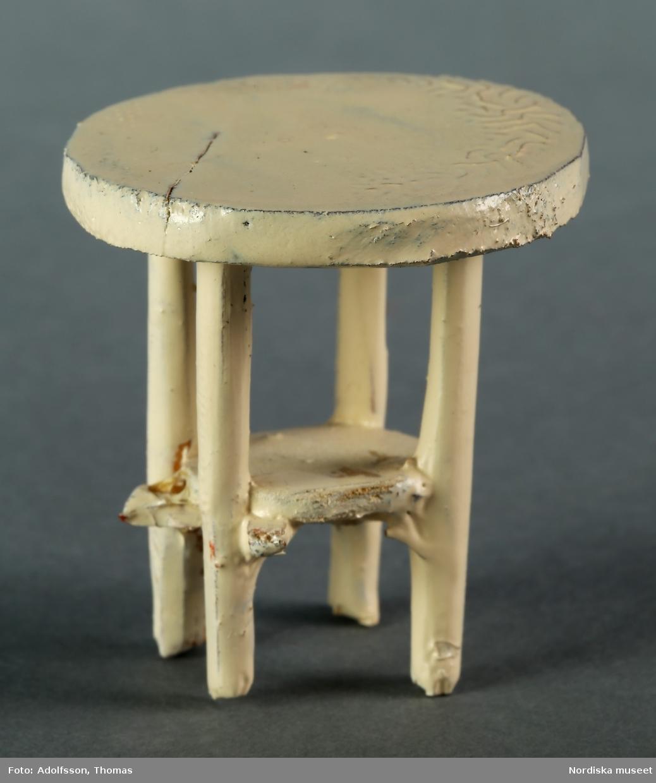 Soffgrupp bestående av soffa, bord och matta som hör till flickrum på översta våningen i dockskåpet. Soffan är tvåsitsig med stomme av trä och klädd med blommigt bomullstyg. Rosa och grönt mönster mot vit botten. Bordet är runt och målat i vitt. Mattan är av mönstrad bomullsfrotté. Till soffan hör d-e) två turkosa kuddar.