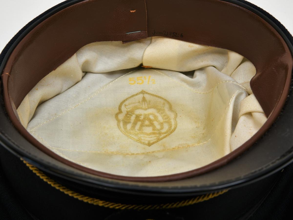 Skärmmössa med mörkblått kapell av diagonaltyg. Mösstränsknappar med motiv av SJ:s bevingade hjul krönt av en krona. Träns av guldfärgat snodd fäst i knapparna. Mössband av svart räfflad textil. På mössbandet sitter ett mössmärke av skinn, klätt i textil, med SJ:s bevingade hjul samt tre kronor krönt av en krona broderat av guldfärgad tråd. Skärmen är tillverkad av skinn med svart lack. Svettbandet är av brunt skinn och insidan är klätt av skumgummi, fodret av vitt bomullstyg. På fodret återfinns ett guldfärgat tillverkningsmärke i tryck samt ett storleksmärke i gult. Tillverkarmärket är täckt av en plastficka.