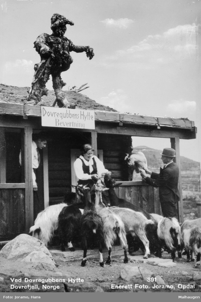 Dovregubbens hytte, med trefiguren Dovregubben på taket. Geit blir matet på trappa