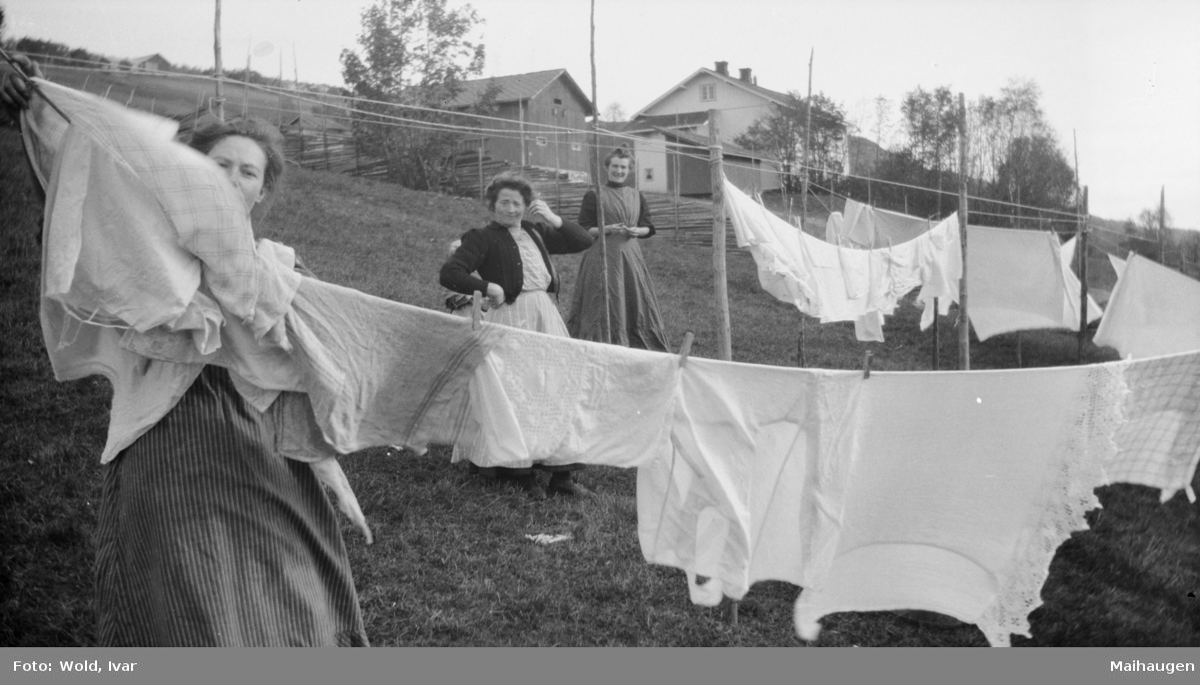 Tre kvinner henger opp klesvask, antatt på Linjordet i Østre Gausdal