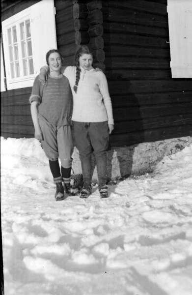 Øksendalen. Gruppe nr. 2 fra Gudbrandsdal Fylkesskole. To kvinner i skiantrekk utenfor tømmerhytte med torvtak. Vinter.