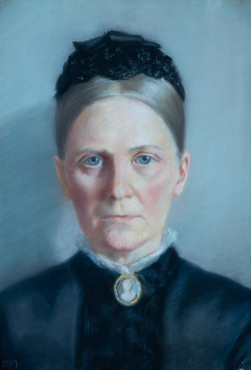 Portrett av Marie Blom,  f. Mangor (1837-1917),  1889.  Kvinneportrett en face,  lyst grått hår med midtskill, sort kappe.  Avskåret over skuldrene.   Sort kjole, smal hvit rysj i halslinningen. Hun har på seg brosje med miniatyr  AAMB 1174, antagelig av hennes mors farmor Sara Juell  f. Chrystie. Grå øyne, rødlig karnasjon, lys grå  bakgrunn.