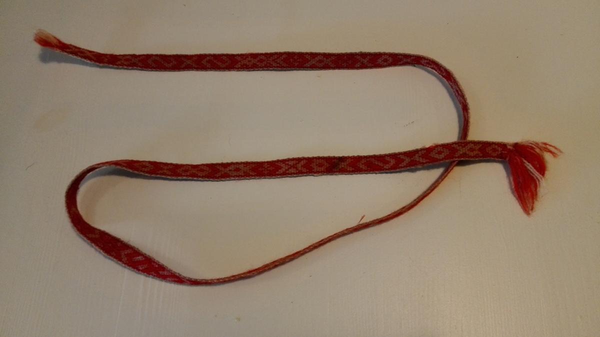 1par strömpeband  Et par strömpeband vævet i baandgrind av hvit og röd uldtraad.  Har dusker i enderne, 1m lang.  Kjöpt av Johannes Mölmedal, Lavik.