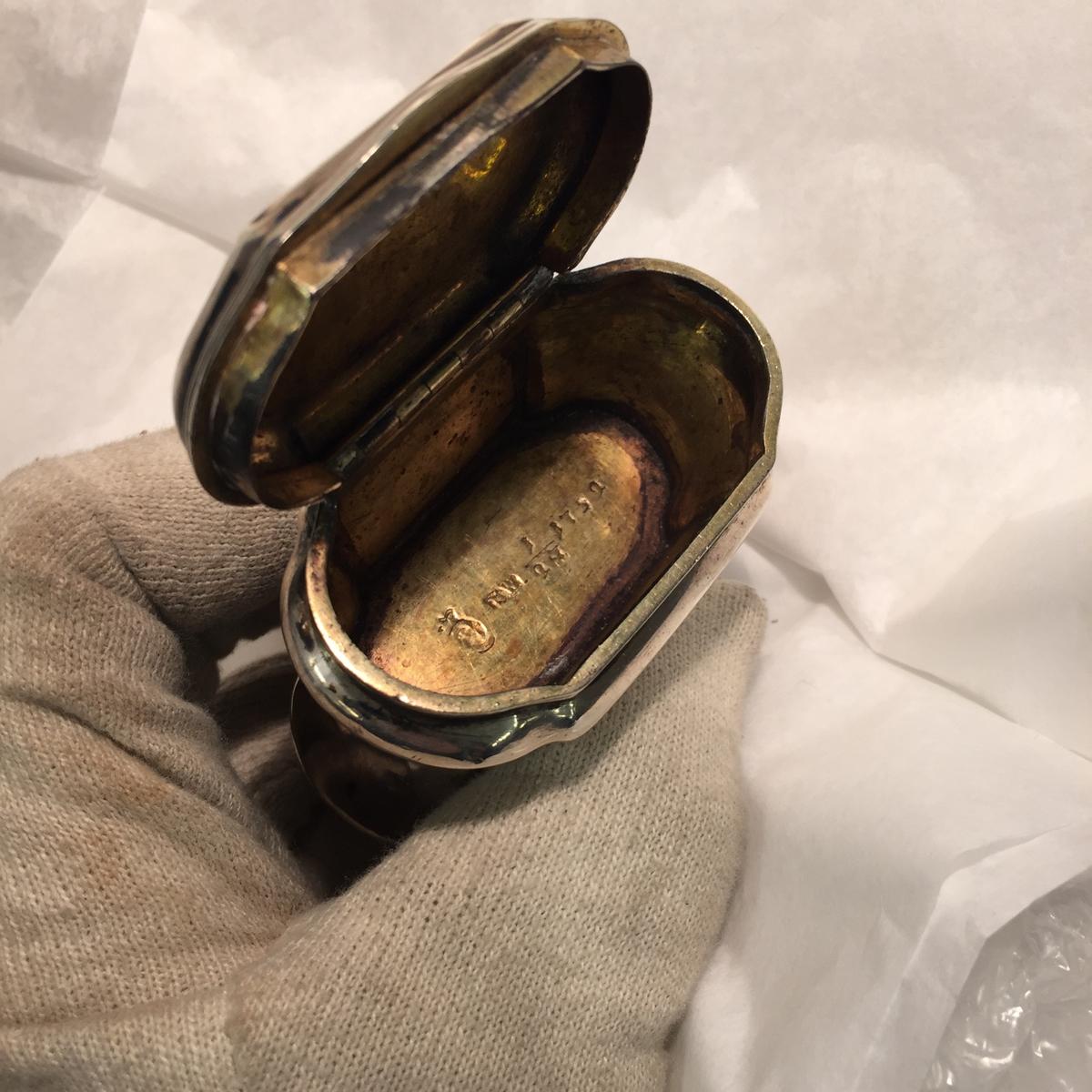 Snusdosa av silver. Invändigt förgylld. Släta konkava sidor och vertikala åsar. Dubbeldosa med lock i båda ändar.