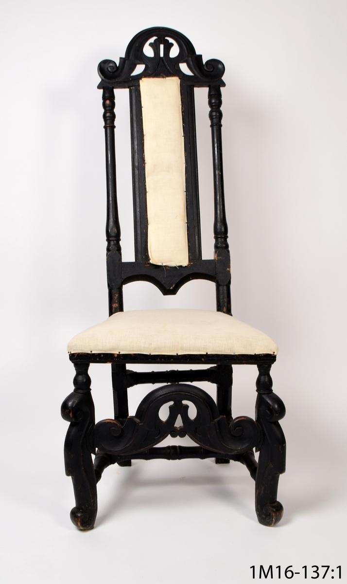 Svartmålad barockstol, skulpterade ben, frambenen med voluter upp och nedtill. Profilsvarvning på frambenens övre del samt på stolens kryss. Bakbenen 4-sidiga nedre delen ngt svängd.Skulpterad tvärslå mellan frambenen med voluter inneslutande bladornament. Smal ryggbricka, profilsvarvade ryggstolpar. På krönet samma skulpterade ornament som på tvärslån på frambenen. Stoppad sits och rygg och klädd med  vitt resp blårandigt tyg.  Inköpt på auktion för 20 kr.