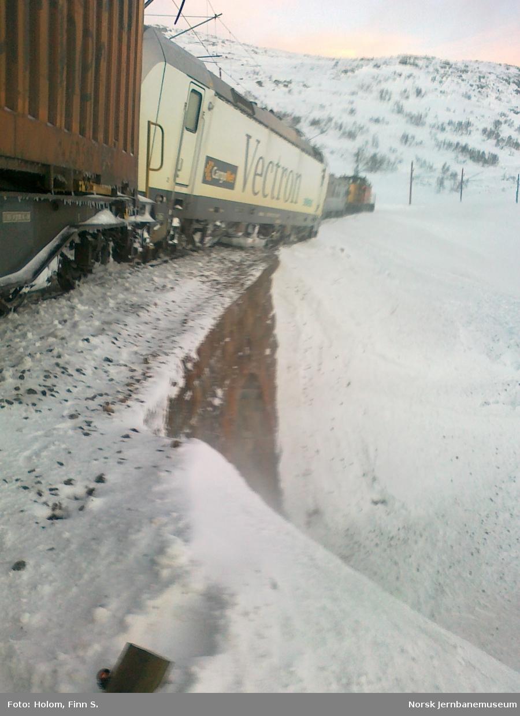 Elektrisk lokomotiv type BR 193 Vectron med godstog 5502 fra Bergen til Oslo har sporet av ved Grytå mellom Finse og Haugastøl. I bakgrunnen skimtes redningstoget med diesellokomotiv type Di 8.