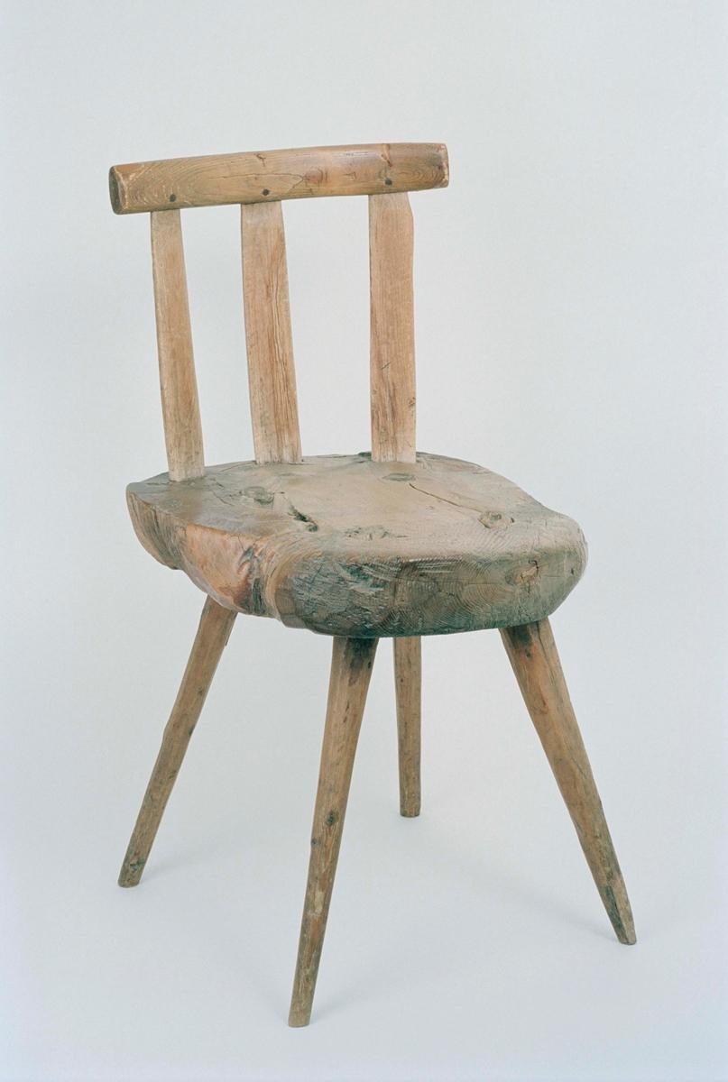 """Stol av trä, sits skuren ur kärnan av en furustock, med sidorna obehandlade. 4 runda utställda ben. Rygg med 3 ryggståndare. Under sitsen inskuret """"1837"""" samt ett bomärke, på en av ryggståndarnas baksida inristat """"A A""""."""