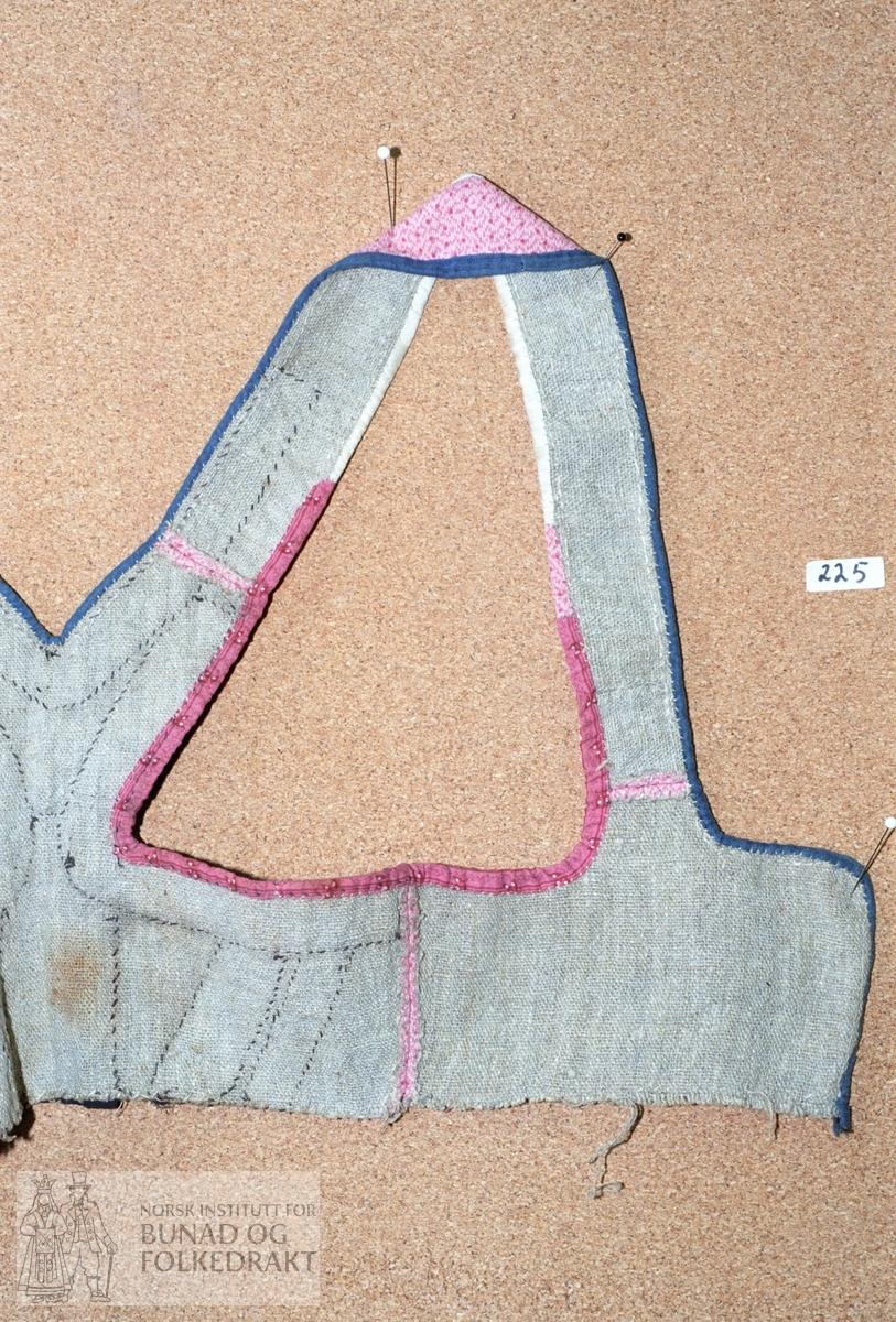 Matr.:  Trykt bomullslerret i kvitt, raudt og rosa. Kanta bak med eit anna trykt bomullsty i raudt og rosa. Kanta framme og i halsringing med blått og grått, smalstripa bomull. Selane er elles kanta med kvitt bomullslerret. Fôr av grov linlerret. Livet har stavar og band av brunsvart fløyel. Livet er sydd for hand med ubleika og bleika lingarn. Storleik:  Sjå skisse.