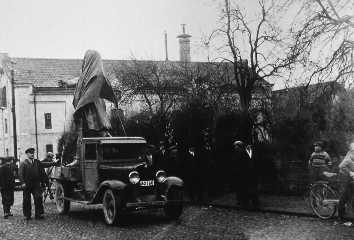 Den riktiga Engelbrektstatyn transporteras, på ett lastbilsflak, till sin placering intill entrén till Heliga Trefaldighetskyrkan. Några nyfikna tittar på. Den staty som avtäcktes i samband med Riksdagens 500-årsjubileum, 27 maj, var gjord av gips.