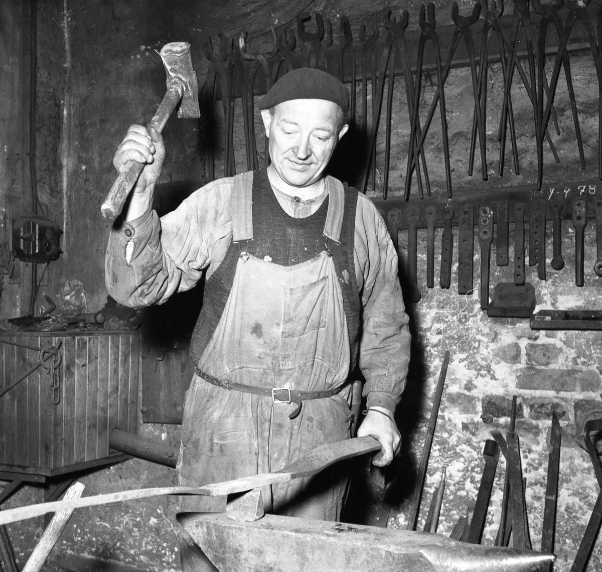Albin Zander, smed på Jäders bruk. Man klädd i basker och förkläde. Han håller ett verktyg i handen. På väggen hänger tänger och andra verktyg. Han befinner sig i smedjan.  Bilden togs, till en artikel i Arboga Tidning, som handlade om kommunsammanläggningen.