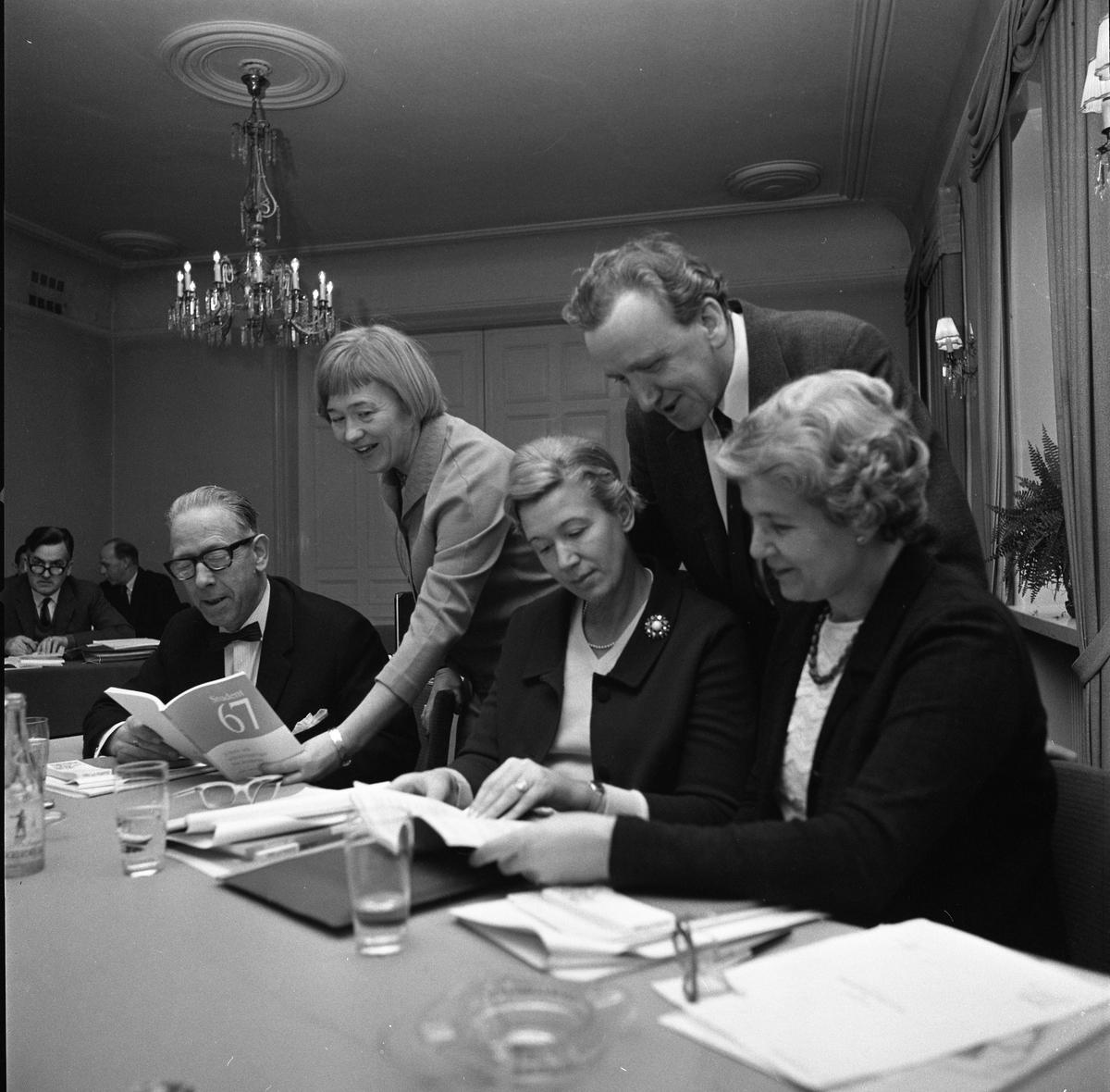 Arbetsförmedlare på konferens. Tre kvinnor och fem män i vacker lokal. Ljuskrona i taket, vattenglas och papper på borden.