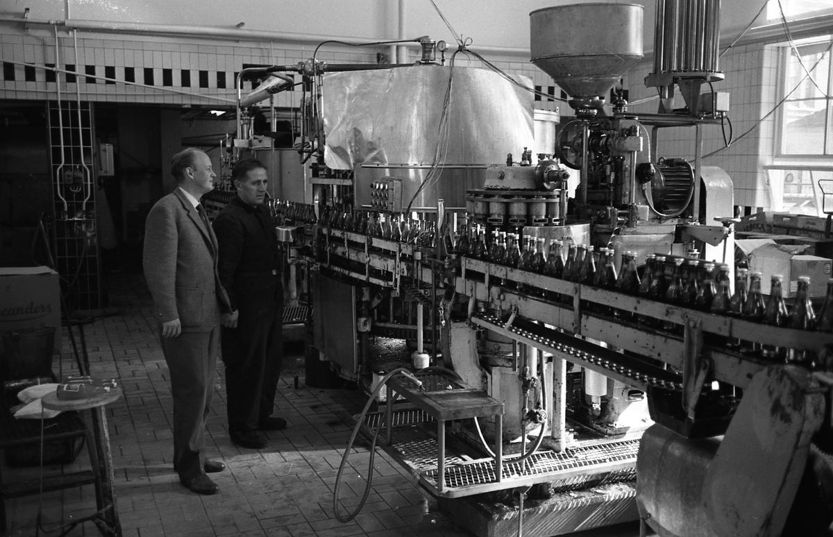 Arboga Bryggeri, interiör. Två män, den ene i kavaj och slips, den andre i overall, står vid ett löpande bland med flaskor. Väggen bakom dem är kaklad. Fönstren, mitt emot, släpper in mycket ljus. Ture Anderberg (bryggmästare, till vänster) och Stig Henriksson övervakar när ölen tappas på flaskor.  Anläggningen var färdigbyggd 1899 och verksamheten startade 1 november samma år. 24 oktober 1980 tappades det sista ölet, på bryggeriet. Märket var Dart. Läs om Arboga Bryggeri i hembygdsföreningen Arboga Minnes årsbok 1981
