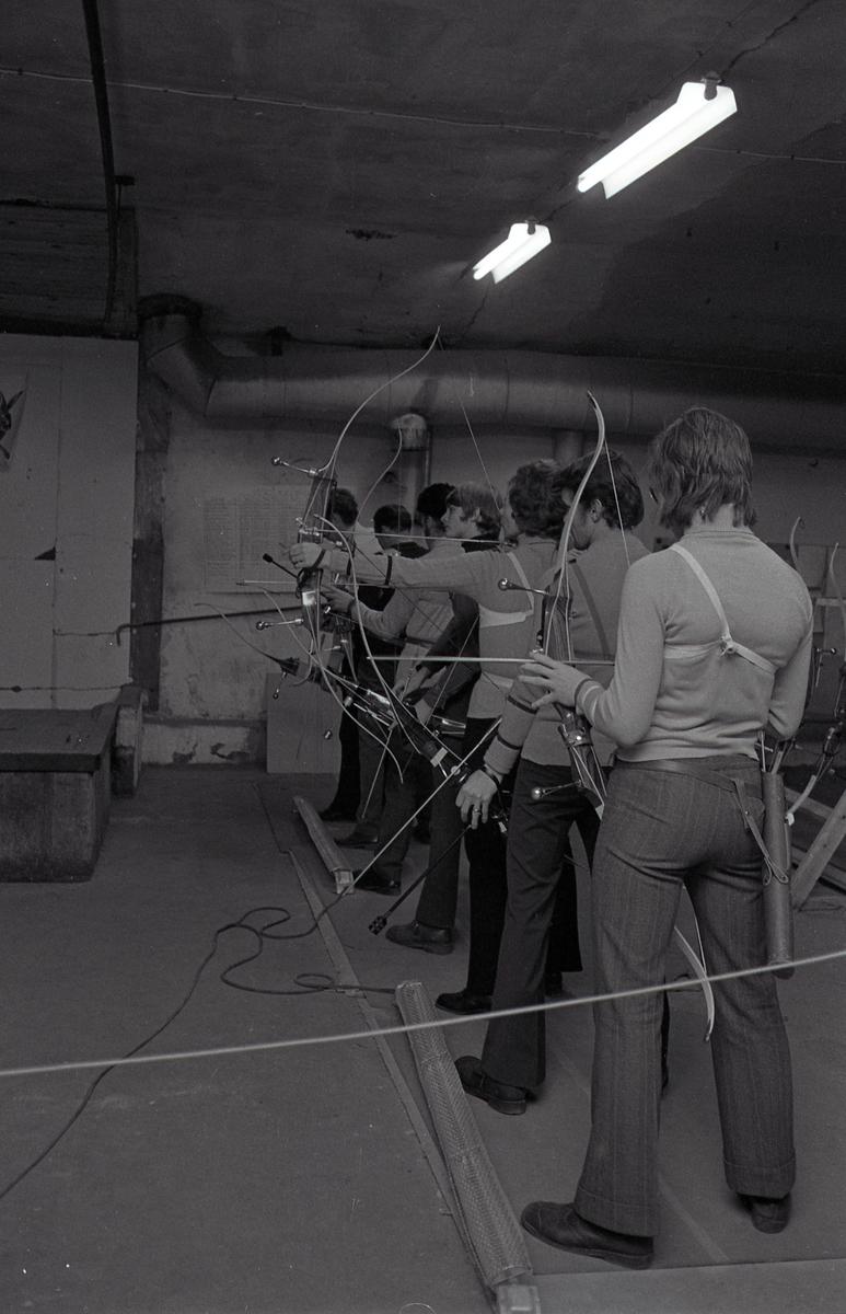 Inomhusträning hos Arboga Bågskytteklubb. Sju personer står, bredvid varandra, med pil och båge. De skjuter mot måltavlor på väggen utanför bilden. Var och en har sitt koger hängande vid höften. Framför fötterna ligger två värmeelement. Lokalen ser ut att ligga i en källare. Den tredje personen, från fotografen räknat, är Kerttu Klotz.