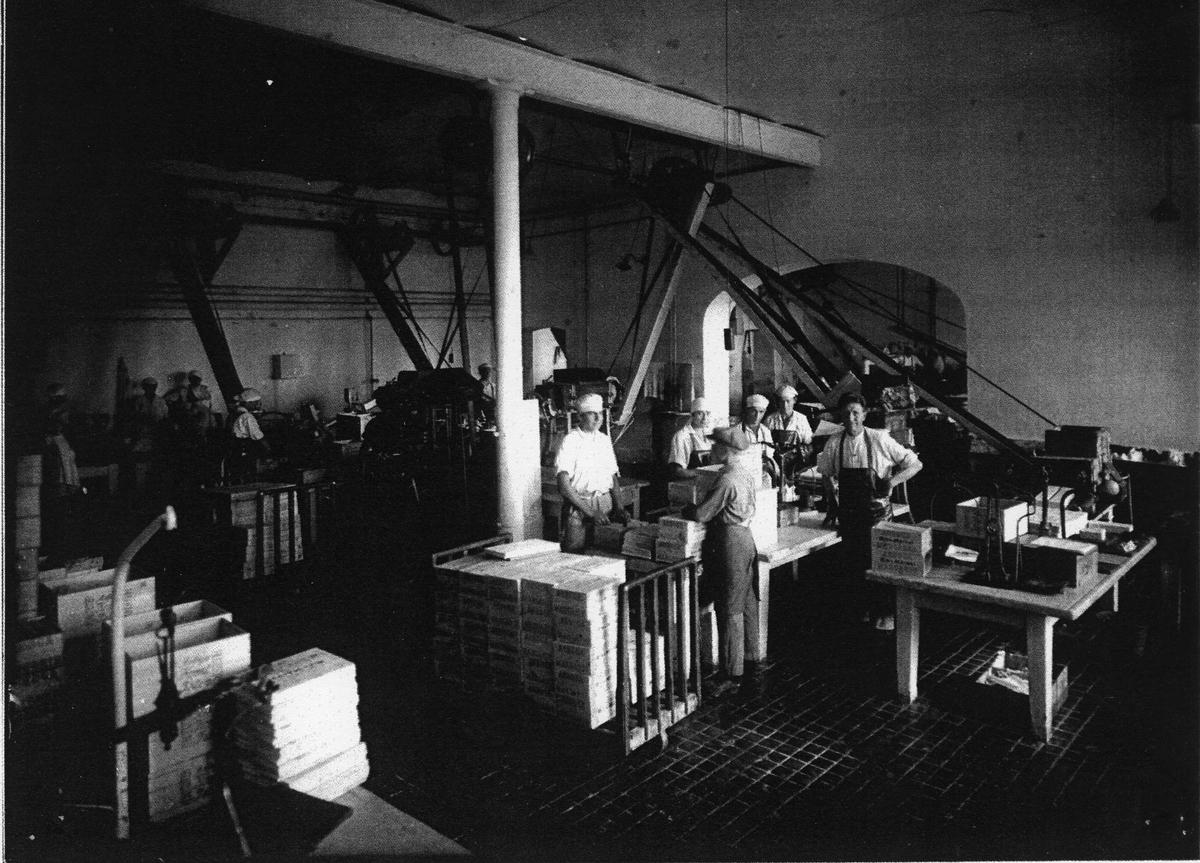 Arboga Margarinfabrik, interiör. Förpackningsavdelningen. Människor arbetar i en fabrikslokal, de har arbetskläder och mössor. Trälådor syns i förgrunden. 1920-talet  Bilden är utskriven på vanligt papper. Läs om Arboga Margarinfabrik i Arboga Minnes årsbok 1978