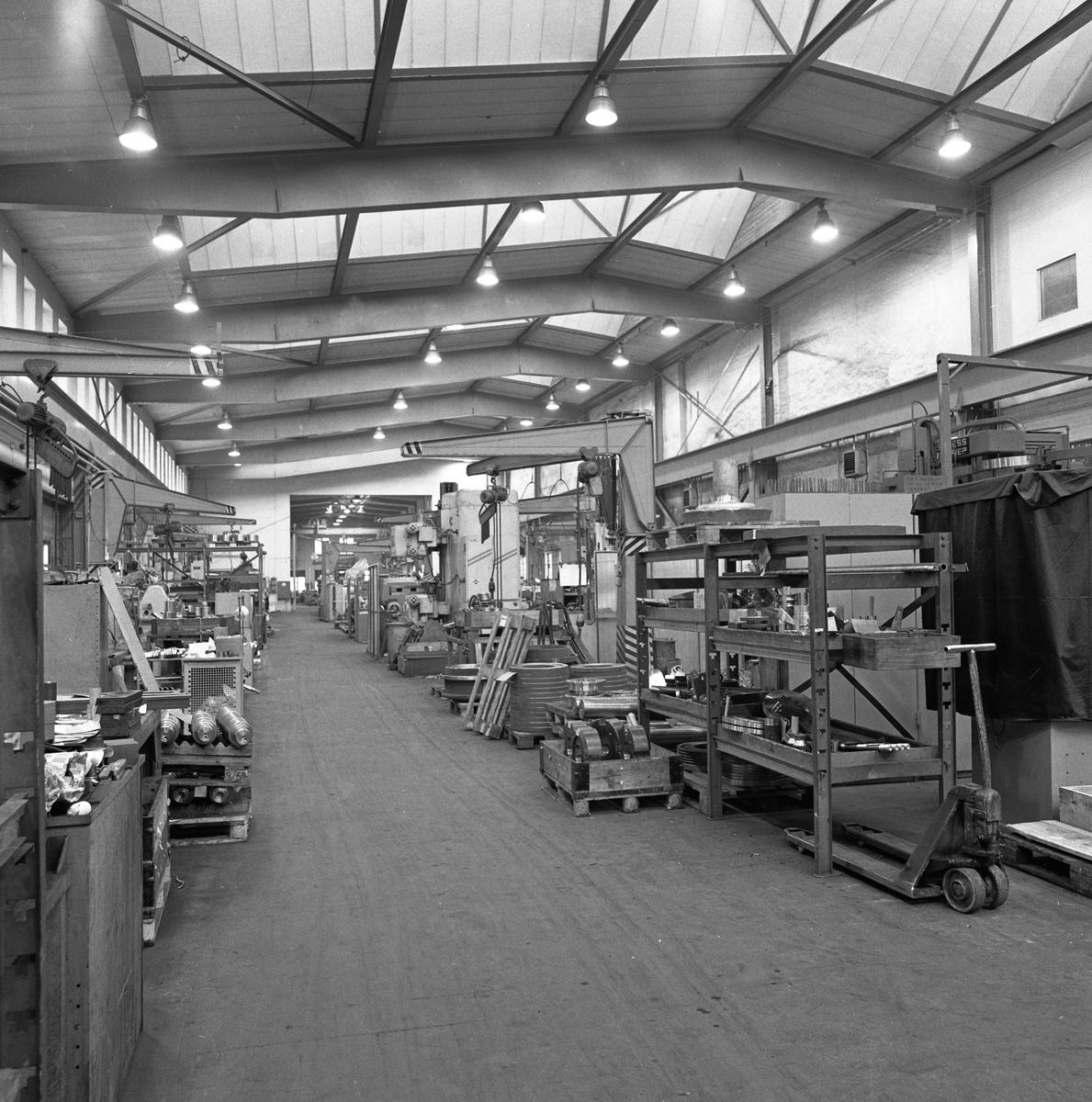 Arboga Mekaniska Verkstad, Meken, interiör.  Fabrikslokal med maskiner och hyllor med maskindelar. 25 september 1856 fick AB Arboga Mekaniska Verkstad rättigheter att anlägga järngjuteri och mekanisk verkstad. Verksamheten startade 1858. Meken var först i landet med att installera en elektrisk motor för drift av verktygsmaskiner vid en taktransmission (1887).  Gjuteriet lades ner 1967. Den mekaniska verkstaden lades ner på 1980-talet. Läs om Meken i Hembygdsföreningen Arboga Minnes årsbok från 1982.