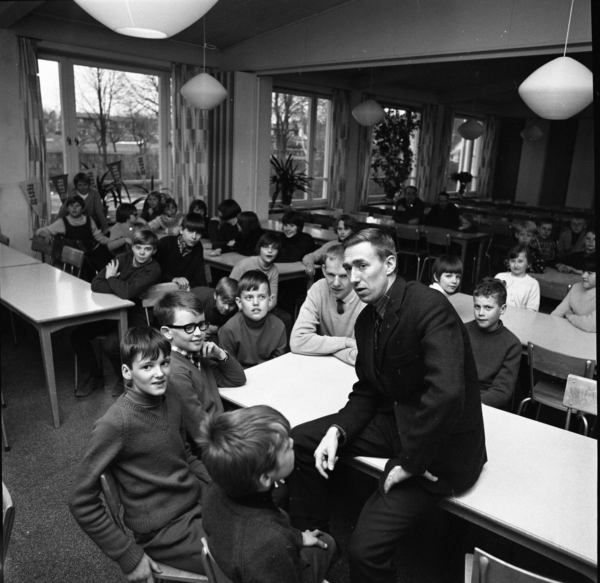Arboga Orienteringsklubb har ungdomsträff. Lennart Öberg talar med barn som samlats i Gäddgårdsskolans matsal.  Bakom Lennart sitter Hans Ekberg. Han är slöjdlärare och orienterar på fritiden. Långt bak i lokalen sitter två män.