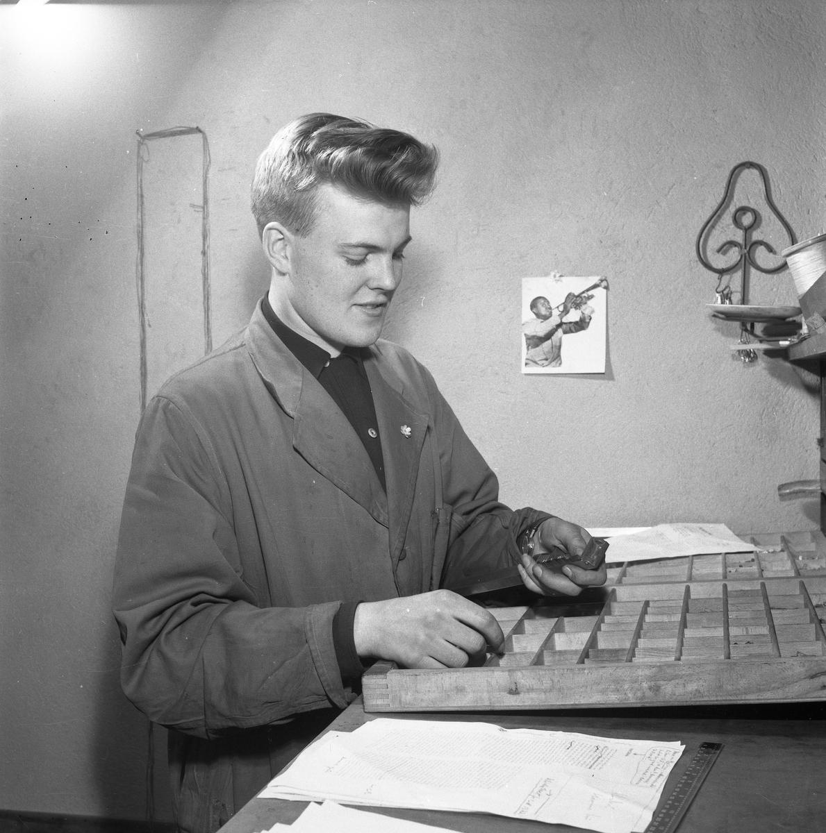 Arboga Tidning, personal och interiör. Ung man, iklädd skyddsrock. Han är möjligen typograf. På väggen bakom honom sitter en bild på trumpetspelaren Louis Armstrong.