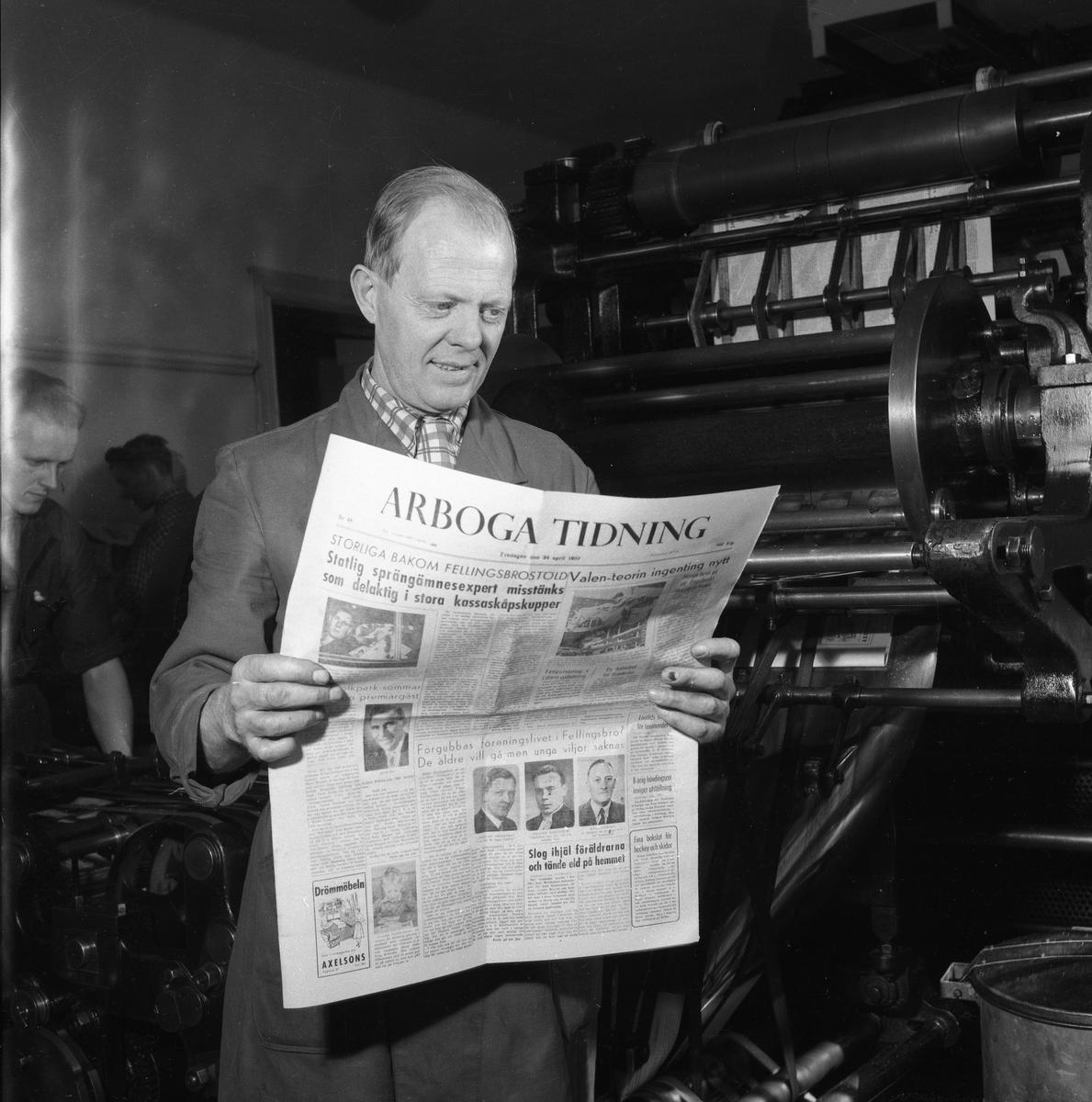 Arboga Tidning, personal och interiör. En man håller i en färsk upplaga av tidningen. Han är klädd i arbetsrock och står intill en tryckpress. Två andra män skymtar i bakgrunden.