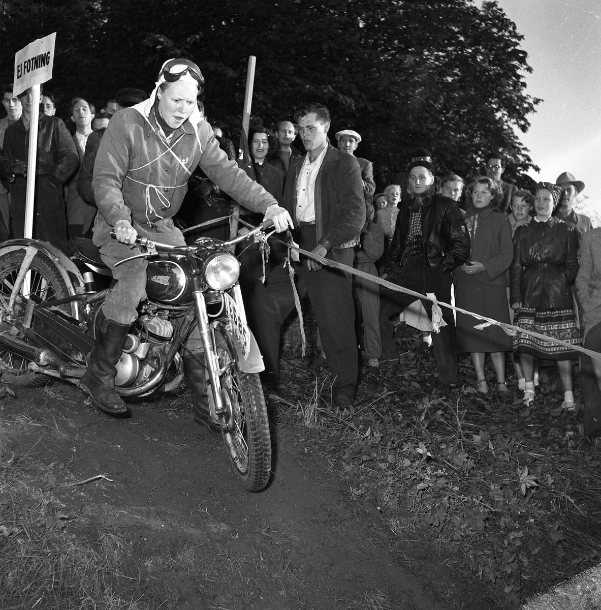 Arbogas Stjärnknutte. Tävling i terrängkörning med motorcykel. Publiken, kvinnor och män, står alldeles intill banan.