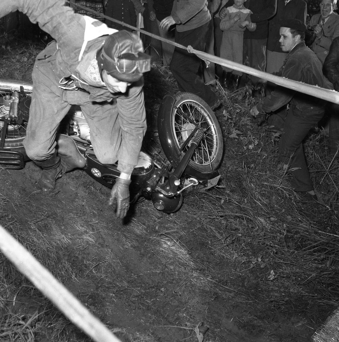 Arbogas Stjärnknutte Tävling i terrängkörning med motorcykel. En man har kört omkull. Han har vindglasögonen i pannan. Publiken står alldeles intill i backen.