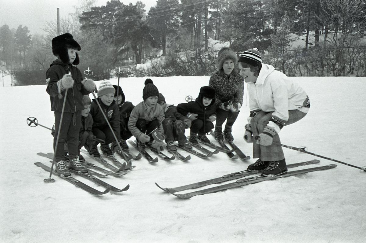 Avslutning på skidskola för barn. Två kvinnliga skidlärare och sju barn. Anita Gustafsson är skidläraren i spräckliga jackan.