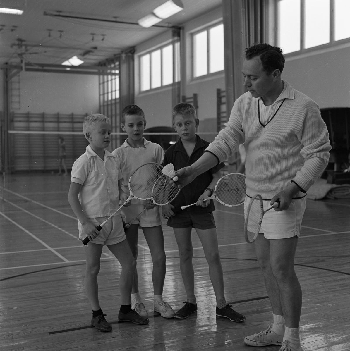 John Erik Kihlström håller badmintoninstruktion med Thomas Liljehammar, Thomas Kihlström och Rolf Mattsson i Gäddgårdsskolans gymnastiksal.  Lektion i badmintong. En man instruerar tre pojkar. Alla har ett racket i handen. De befinner sig i Gäddgårdsskolans gymnastiksal.