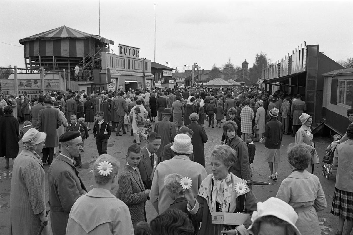 Barnens Dag firas av människor i alla åldrar. Karusell och lottstånd lockar en stor publik till festområdet på Sturevallen. I förgrunden står en kvinna och säljer Barnens-Dags-blomman. I bakgrunden syns tornet på Sankt Nikolai kyrka.