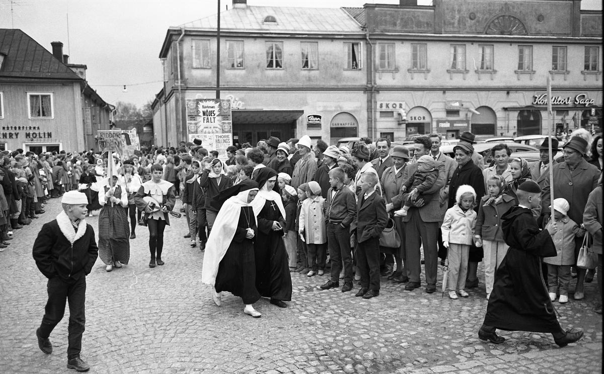 """Barnens Dag firas med en parad genom staden. Här kommer utklädda barn gående över Stora torget; en munk och två nunnor följda av """"Riddartiden"""" med lutspelare. Många människor har samlats för att se på. Henry Molins motorfirma och Café Saga skymtar i bakgrunden."""