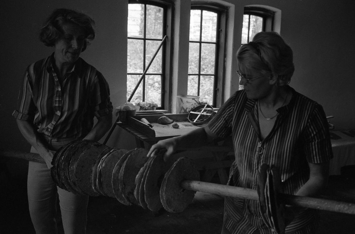 Brödbakning vid Jäders bruk. Två kvinnor i en bakstuga/bagarbod. De håller en stång med uppträdda knäckebröd mellan sig. Vid fönstret finns ett bakbord med brödkavel, bunke och brödkavel.