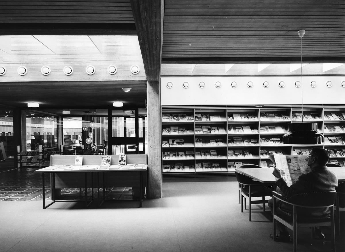 Arboga Stadsbibliotek, interiör. Entrén till biblioteket ses till vänster. Till höger står hyllorna med tidskrifter. En man sitter och läser en dagstidning vid det stora bordet. De stora fönstren, mot Arbogaån, ligger utanför bilden, till höger.