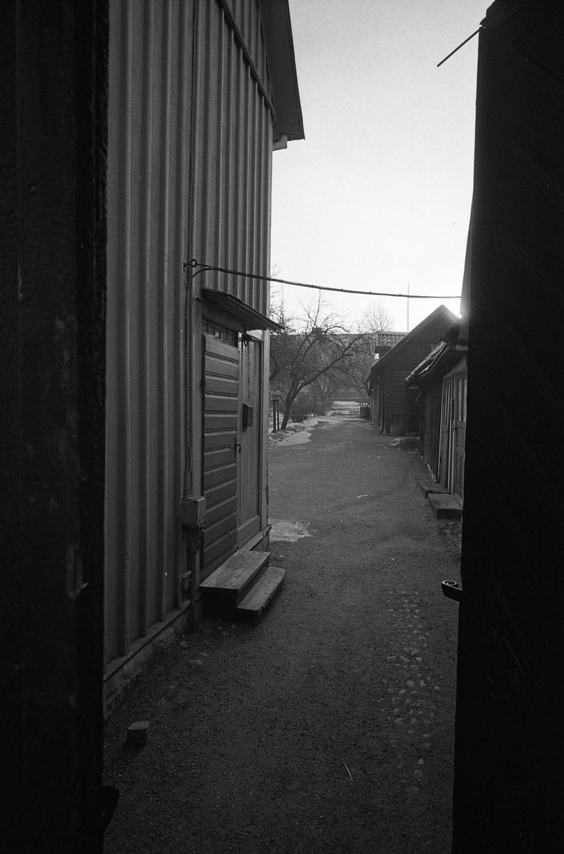 Miljöbild från äldre bebyggelse i kvarteret Tullnären, mellan Storgatan - Trädgårdsgatan och Herrgårdsgatan - Paradisgränd. Boningshus till vänster och uthus till höger. Fotografens anteckning: Dokumentation av fastigheter i kvarteren söder och norr om ån. Bilder och beskrivning finns på Arboga Museum.