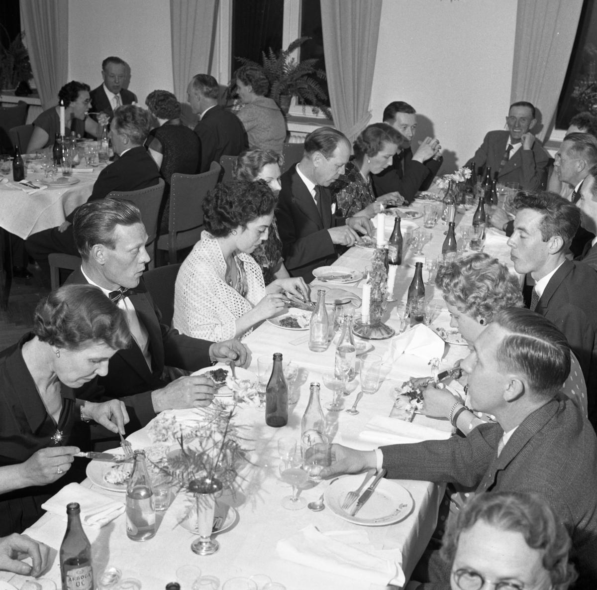 Elektrikerförbundets Arbogaavdelning har jubileumsfest. Män och kvinnor sitter till bords och äter. Borden är dukade med blommor i vas och ljusstakar. Herman Skoglund (nästan mitt i bild) med näsduk i fickan. Snett mitt emot honom, ses profilen på Gustav Danielsson.