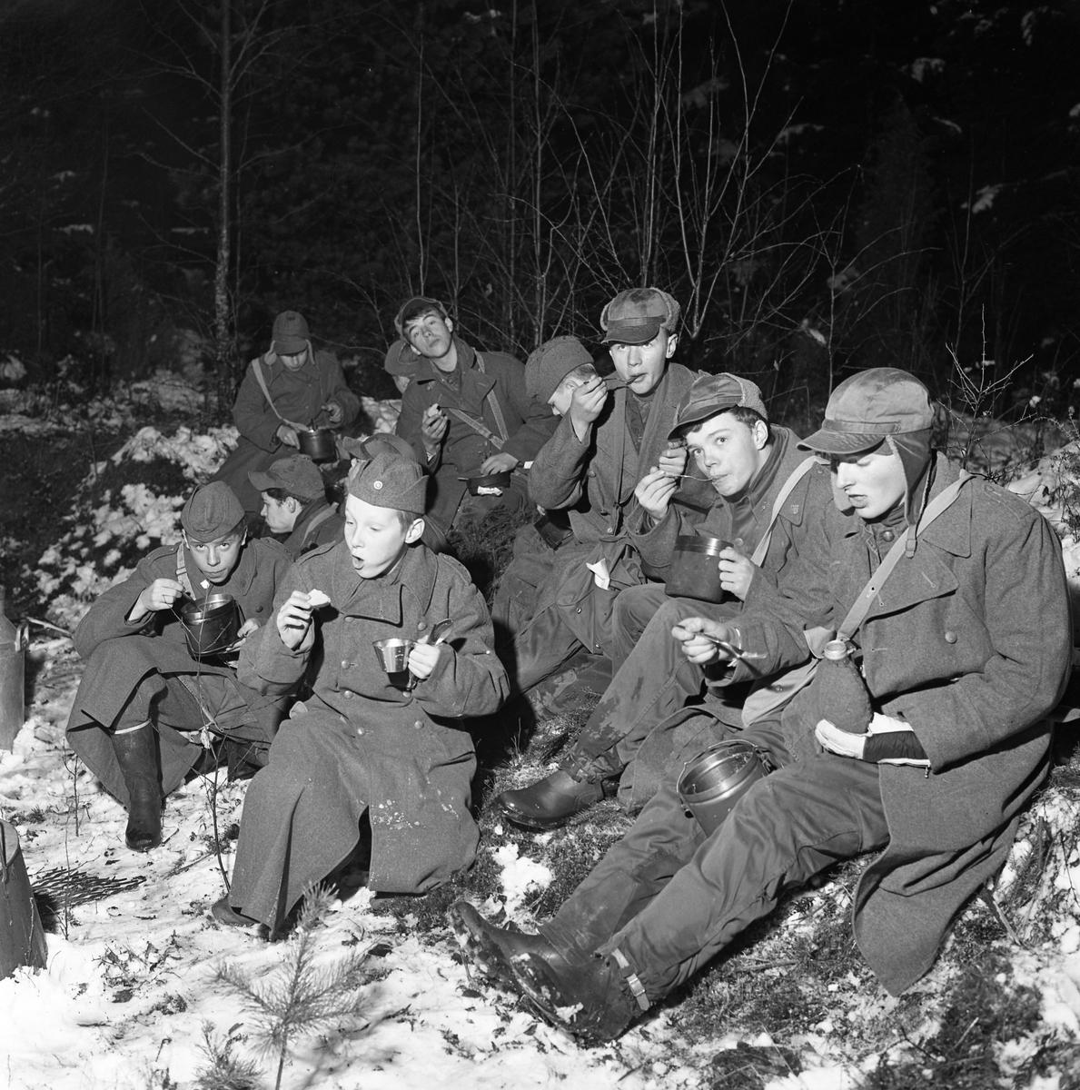 FBUl-ungdom övar i skogen. Grabbarna är klädda i yllerockar och mössor med öronlappar. Pojkarna sitter på granris och äter ur sina plåtburkar. Det är vinter och snö. Frivillig Befälsutbildning.