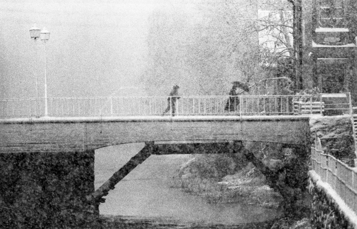 Två personer kämpar sig fram över Kapellbron, i kraftigt snöfall. Den ena personer har ett paraply. Till höger skymtar trappan ner till Labron/Ladbron/Lastbron