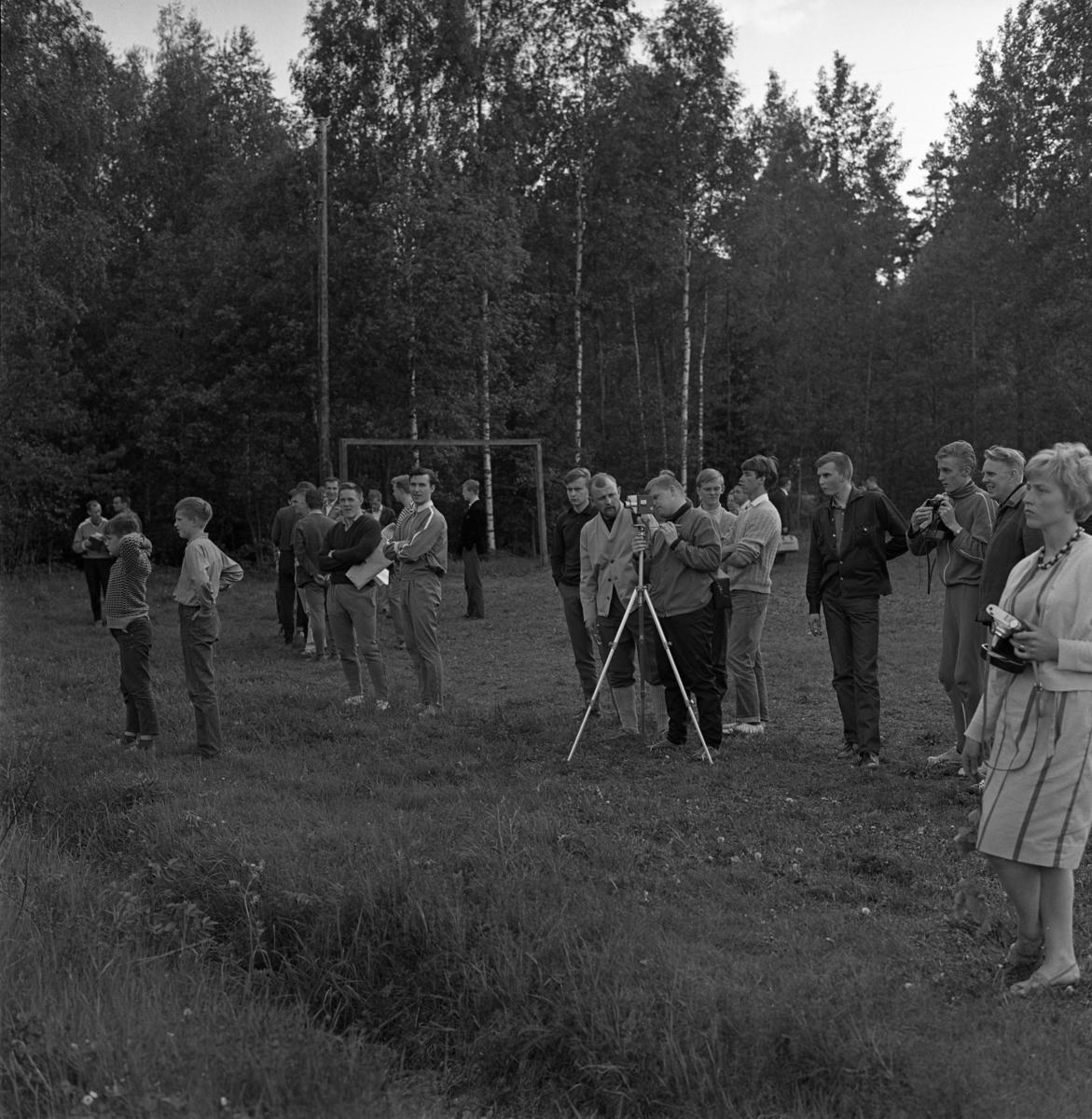 Tele-kaveln, orienteringstävling. Här står publiken, i skogskanten, med kameror och filmkameror i högsta hugg.
