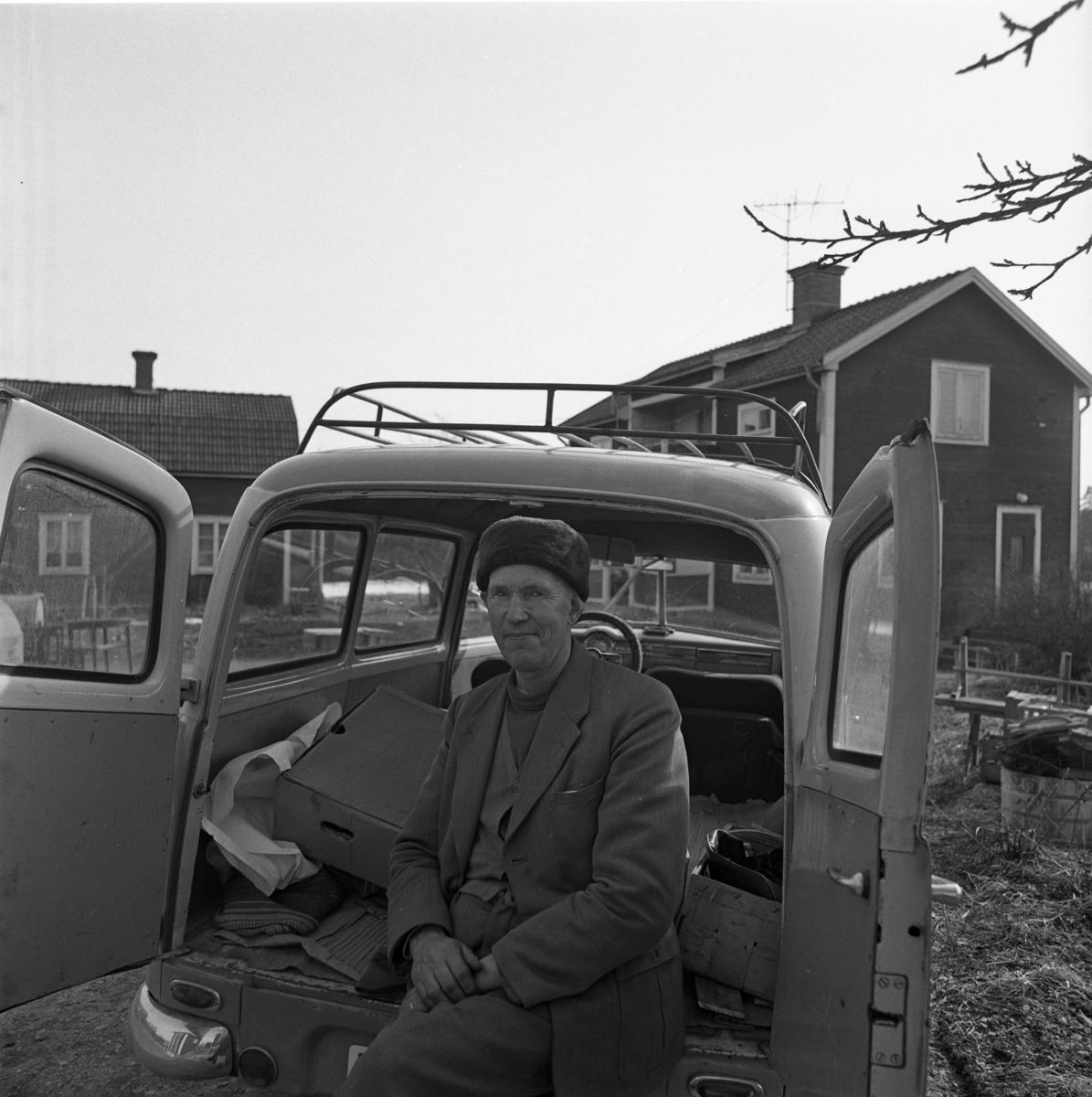 Tore Andersson i Mossen. Han sitter i bakluckan på sin Amazon kombi och har en krimmelmössa på sig. Bakom bilen ses två boningshus.