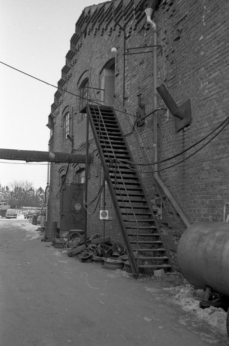 Trappa på gaveln av Arboga Margarinfabrik. En del av byggnaden används nu som bilverkstad. Några däck ligger under trappan och bilar ses i bakgrunden.