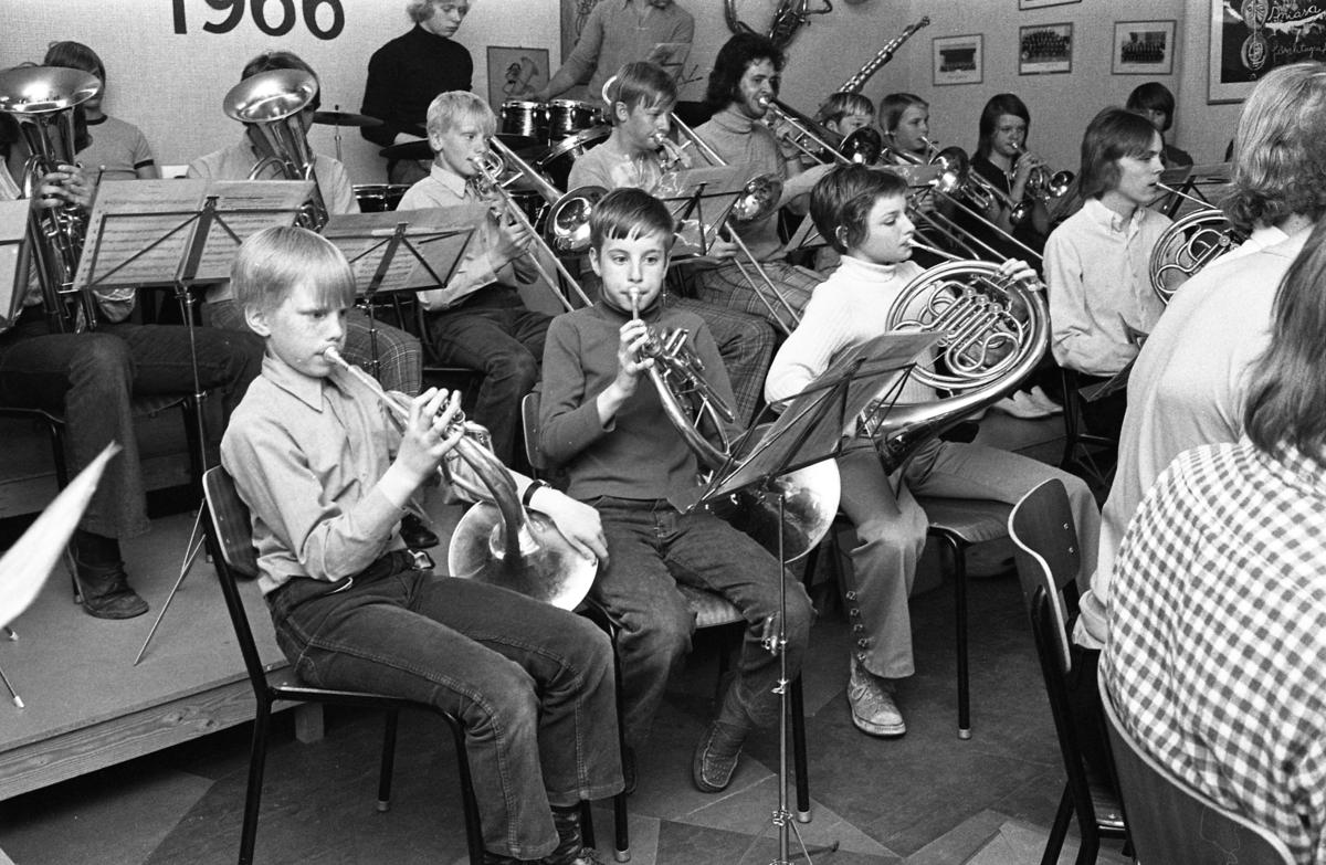 Ungdomsorkestern repeterar; valthorn, trombon, kornett, tuba och batteri spelas. De fyra grabbarna med valthorn är: Göran Torshage, Anders Garpered och Anders Kjellberg och Arne Eriksson. Trombonist nr två är Peter Jäderlund och nr 4 är Anders Evaldsson. På trumpet, Margareta Hjelm och kornett Marita Carlsson. Batterist är Per Pukonen. Längst upp i hörnet sitter två flickor och spelar kornett. Den blonda heter Margareta Hjelm och den mörka heter Marita Carlsson Blåsorkester.