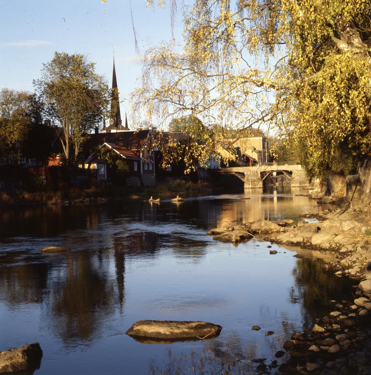 Vy mot Kapellbron och Heliga Trefaldighetskyrkan. Lågt vatten i Arbogaån. Kvällssol på sommaren. Bilden är tagen från en brandgata från Storgatan (södra sidan om ån).