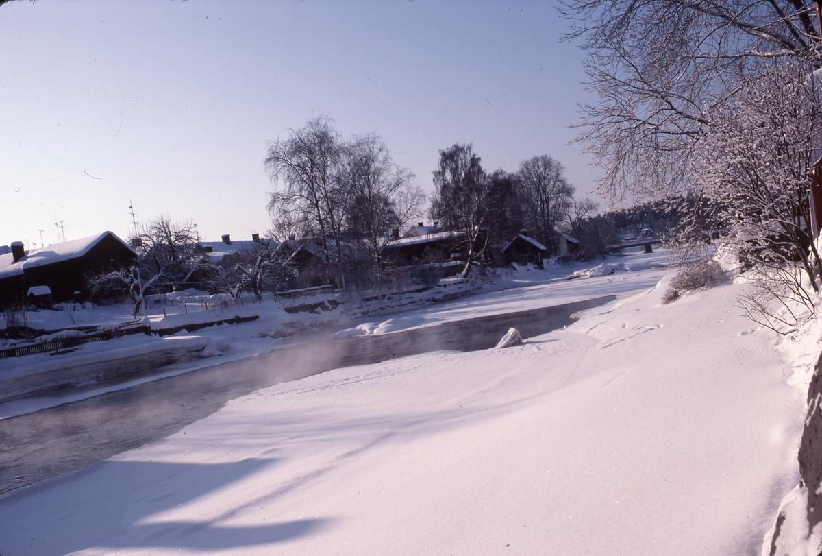 Vintervy över ågårdar på södra sidan av Arbogaån. I bakgrunden ses Strömsnäsbron. Is och snö på ån.
