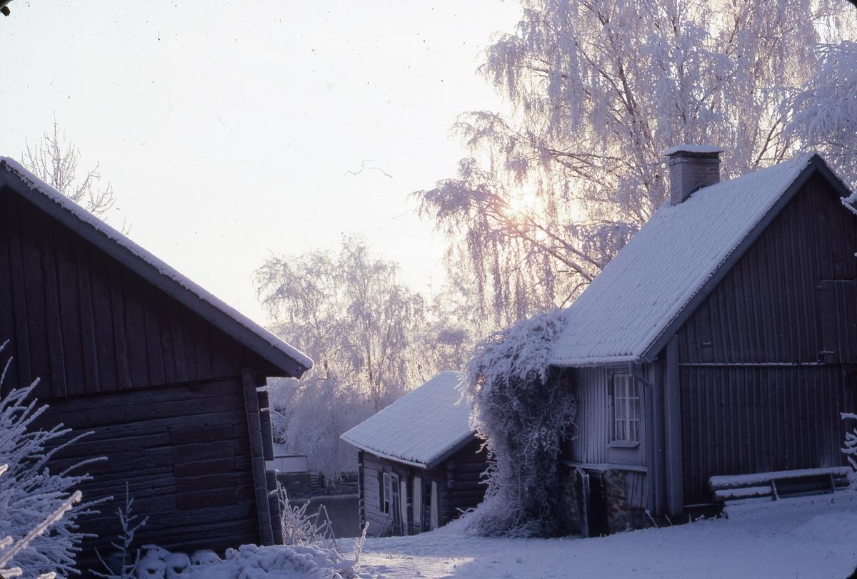 Ågårdar på Arbogaåns norra sida, längs Västerlånggatan. Det är vinter och snö.