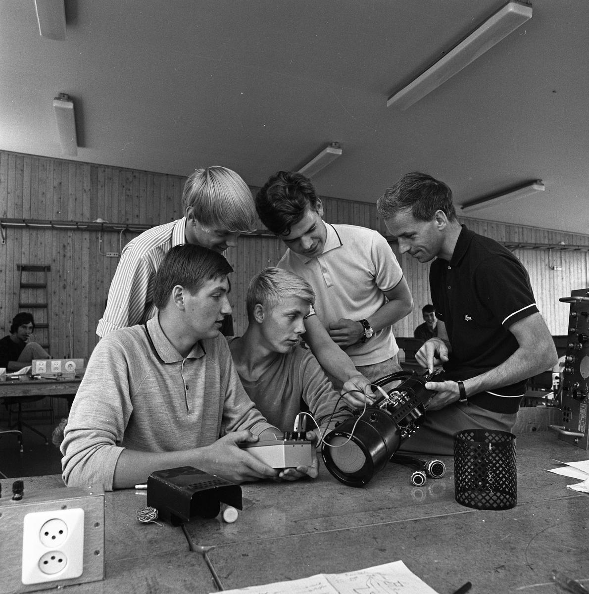 Yrkesskolan. Lärare Åke West tillsammans med elever. De båda stående eleverna är: okänd och Hans Hellberg De båda sittande eleverna är: Bengt Jonsson (Korv-Jonsson) och Gunnar Franzén De studerar en elektrisk apparat