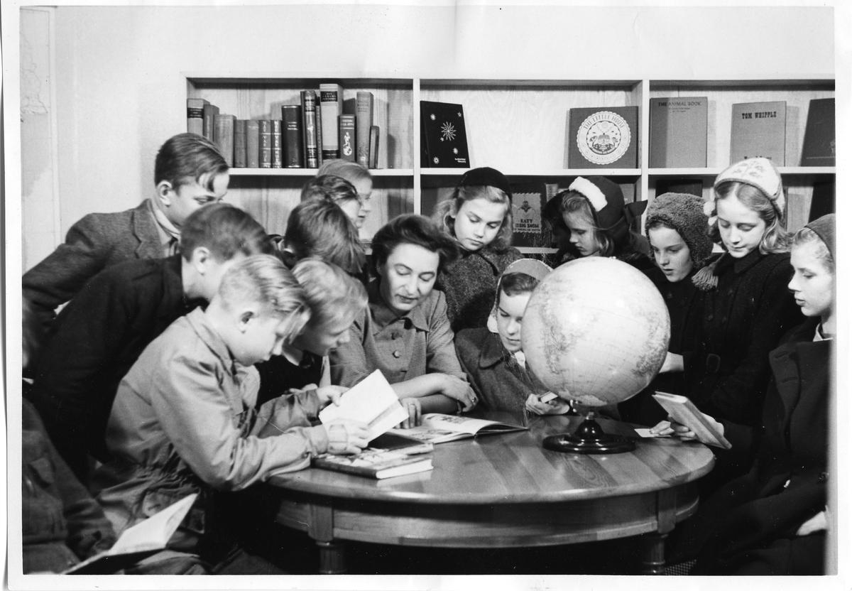 Biblioteket. En kvinna sitter vid ett runt bord. Hon är omgiven av barn. Hon läser ur en bok. Vid sidan om henne sitter en pojke och läser. Flera av barnen har ytterjackor och mössor på sig. En jordglob står på bordet. Bakom barnen står flera bokhyllor mot väggen. Det är böcker på hyllorna. Fotografiets baksida: AKF-14454