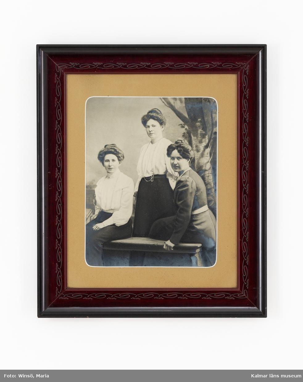 KLM 45619:74. Tavla. Fotografi, i ram, papper, glas, trä. Inglasat foto med träram föreställande systrarna Larsson. Påskrift baksida: Emitz (Gate) Ester. Ester Larsson var Gösta Ahlms mor. Till höger okänd.